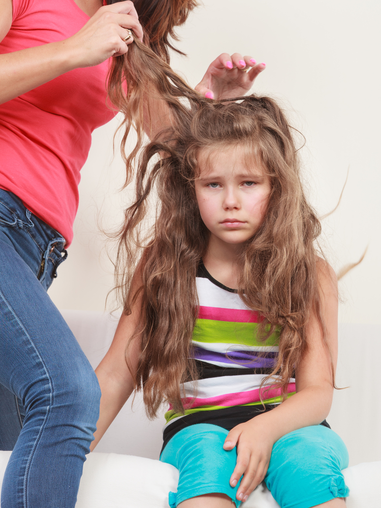 Little girl getting her super lice combed out by her mother