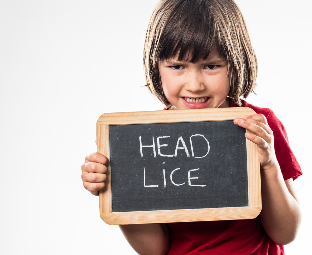 child holding up chalk sign that reads head lice at lice clinics usa