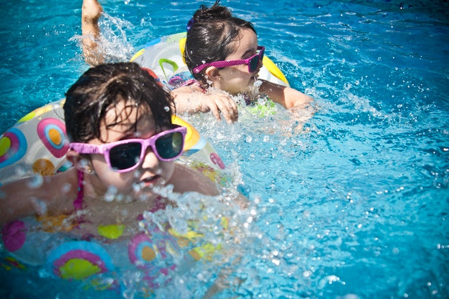 two children swimming in a pool with floaties and goggles on a sunny summer day