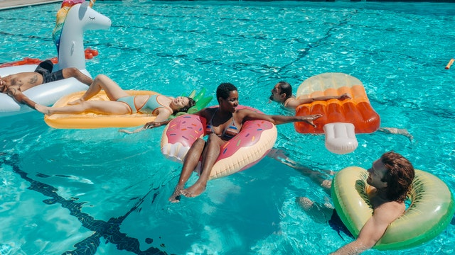 family floating on floaties in swimming pool